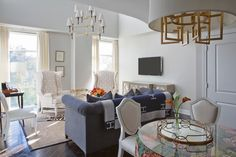 Gorgeous living room features Jonathan Adler Ventana Three Tier Chandelier illuminating a pair of wingback chairs upholstered in Thom Filicia Citysquare Fabric facing blue sofa accented with Hermes Throw Blanket in Dark Blue across from brass and glass coffee table atop zebra rug layered over bound sisal rug.