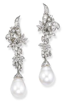 A PAIR OF SOUTH SEA CULTURED PEARL AND DIAMOND EAR PENDANTS   Each set with a detachable drop-shaped cultured pearl measuring approximately 13.30 x 17.70 and 13.50 x 17.90 mm., with a circular-cut diamond cap, to the vari-cut diamond foliate motif and baguette-cut diamond line surmount suspended from a scroll and floral diamond top, mounted in 14k white gold