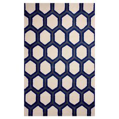 Anchor your living room seating group or define space in the den with this lovely hand-tufted wool rug, showcasing a geometric motif in blue.