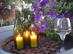 Doing this! Wine bottle candle holders for the deck! Follow this link to learn how to cut the bottoms off the bottles. -  http://diy.weddingbee.com/topic/my-diy-wine-bottle-centerpieces