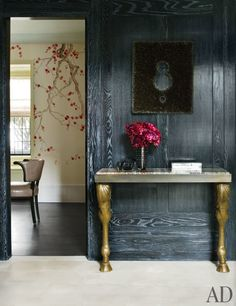 The brass console gives this dark entryway a luxe vibe | archdigest.com