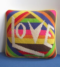 Groovy mod needlepoint pillow in unique 8 x 8 smaller size. White letters spell LOVE over an abstract rainbow design. Backed with yellow pique
