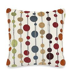 This contemporary toss pillow brings interest and style to any room. Its ivory background features a graphic of intricate chenille circles in varying sizes and rich shades of red, blue, gold, green rust and wine.