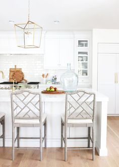 White kitchen with light gray Ballard Designs bar stools and brass accents