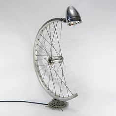 Bicycle Desk Lamp made with a bicycle wheel and gears, with built-in on/off switch. Equipped with bulb fitting and stan.Bespoke Bicycle Desk Lamp made with a bicycle wheel and gears, with built-in on/off switch. Equipped with bulb fitting and stan.