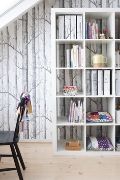 The best way to make a small space feel larger is to incorporate vertical elements. In this case, the woods wallpaper works with the high bookcase. I especially love how nothing went to waste here and the extra paper was used to make book covers. Woods wallpaper is available at walnut wallpaper #wallpaper