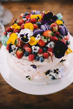 Meringue wedding cake topped with fresh berries and bright edible flowers | Alex Carlyle
