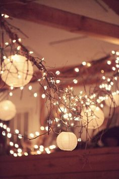 Hanging paper lanterns strung all across the ceiling over the tables with white lights