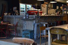 MARCUS Koffie – Ouderwets gezellige #koffiebar. Aan de muur steunt een ouderwetse sjoelbak en hangen oude houten kratten met flessen. Bovenop de bar schitteren potten die de tijd van vroeger nog meer benadrukken. Kortom, MARCUS Koffie weet een pure sfeer te creëren.