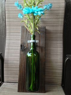 Recycled wine bottle as wall hanging. Add silk or dried flowers for a fabulous look. Can use inside or outside.