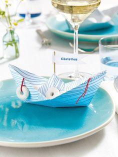 """Damit jeder im richtigen Boot sitzt, können Sie mit Platzkarten Klarheit schaffen. DIY-Tipp: Papierschiffchen, von deren Segeln die Gastnamen """"wehen"""""""