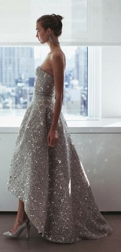 Oscar de la Renta dress, silver sequins on grey, structured sleeveless bodice and full skirt, uneven hemline and long silver chandelier earrings
