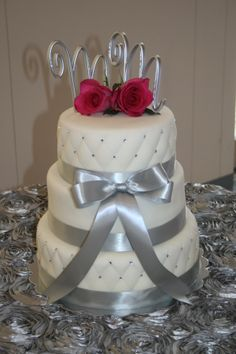 """Wedding Cake Design. Vanilla cake with Chocolate filling, iced with butter cream then covered with marshmallow fondant. Detailed with silver ribbon, pink roses, sparkly rhinestones and the """"M&M"""" for the happy couple."""