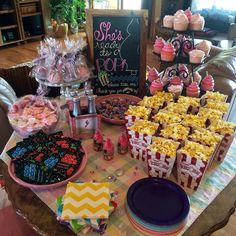 Ready to pop! Baby shower favor table with things that go POP! Lollipops, cake pops, gumballs, popcorn, pop rocks.