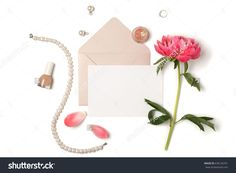 Styled feminine flat lay on white background, top view.Minimal woman's desktop with blank page mock up, envelope, peony flower with petals, pearl necklace, perfume, nail polish. Creative concept