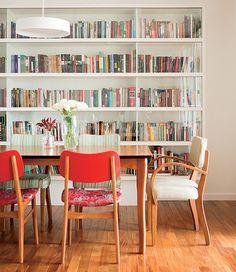 Livros não têm de ficas escondidos. Logo, a arquiteta  Mariana Viegas criou a estante com portas de vidro para a sala de jantar. O ambiente ficou bonito e multiuso