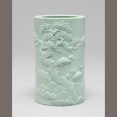 A relief-carved turquoise-glazed brushpot, bitong carved Kangxi four character seal mark, 19th century. Finely decorated with a scene of a crane standing beside a lake, turning its head to look at its mate perched on the trunk of a pine tree beside rockwork, the rim lightly stippled.