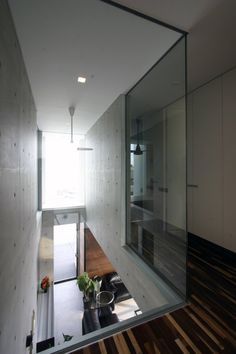 Glass wall opens second floor view of front door and natural light.  'Com Project' by Esprex in Suita, Japan