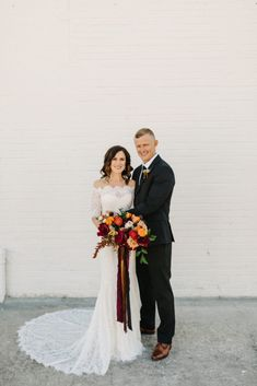 How beautiful is this bohemian wedding day in Lakeland, Florida near Tampa? We love the bride's loose and organic wedding bouquet in shades of burgundy, marigold, ivory, and red with cascading ribbon. Also, how beautiful is her off the shoulder lace wedding dress? | Ashton Events