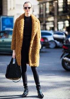 Oversized textured camel coat; black crew neck sweater; skinny black jeans, ankle boots