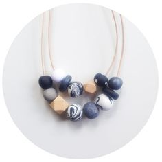 Double stranded necklace featuring handmade polymer clay beads with geometric wooden beads. Leather cord. Chain and clasp fastening. Designed to