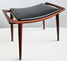 A superbly styled 1950s rosewood or afrormosia foot stool or ottoman, made in Norway and reminiscent of Hans Wegner's Papa Bear stool. The elegantly curved seat retains its original leather-like black vinyl upholstery and features elongated cutout side handles with exposed joinery at the corners, supported on splayed, tapering turned legs. Retains original paper label on underside. A top quality piece with beautiful modernist proportions. Condition is excellent with minor signs of wear…