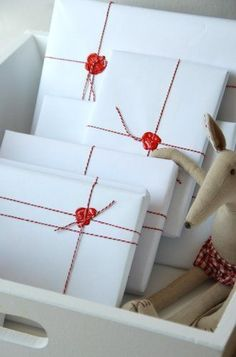 wrapped packages ... clean, simple, classic ... white butcher paper ... red string ... sealing wax over knot ... luv them!!!