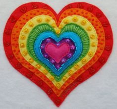 Too fun - felt rainbow heart all decorated and looking pretty. Hang it on the wall or use it as a pin cushion or whatever else comes to mind:)