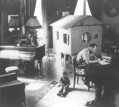 Georges Simenon, French mystery writer, at work beside his child and playhouse.