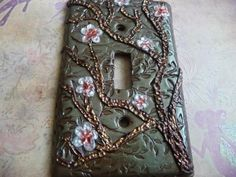 Beautifully designed light switch cover made from Polymer Clay and cast on a metal light switch plate. Sage green decorative back ground with a copper/gold sculpted tree truck. This is for as single light and comes complete with packaged screws for installation.