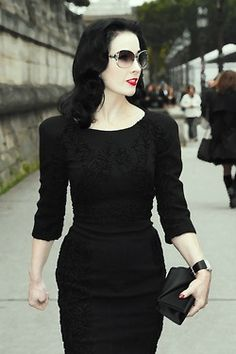 Dita Von Teese in a half sleeve black stealth dress with black detailing on the chest