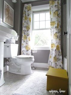Really cute gray and yellow bathroom, with vintage-style floral curtains.