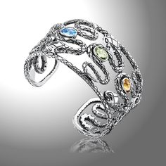 Citrine, Peridot, and Blue Topaz Serpentine Cuff Bracelet - As part of our Serpentine Collection, this elegantly edgy Sterling Silver bangle cuff showcases 9x6 mm Faceted Citrine, Peridot, and Blue Topaz gemstones.