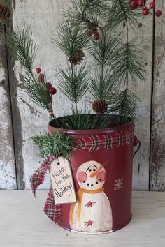 Frosty painted on Vintage Metal Pail Hand painted snowman is antiqued and sealed. Finished with homespun, a sprig of greens, wood tag and snow glitter . The snow flakes go all the way around the pail, use as a center piece once you add your own greens and berries. 7 1/4 T x 6  The current tag says: Home For The Holidays  Customized the wood tag to say: Home For The Holidays, Ill Be Back Again Someday Love Frosty, Winter Tyme, Joy, Believe, Brrr, Frosty, Let it Snow, or your own words. Wood…