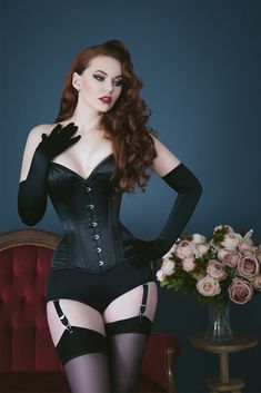 """Do you have a dark side? Emmerald Barwise captured by Tigz Rice wearing our Laurie Corset and Long Satin Gloves. Bring out your inner femme fatale in a sleek black overbust corset by What Katie Did. Our beautiful Laurie style is available in reduced waist sizes 18""""-34"""", with matching lingerie is available. Treat yourself today - glamour is a state of mind. MUAH by Ewa Baberska"""