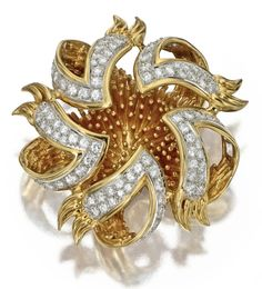 18 KARAT GOLD AND DIAMOND BROOCH, TIFFANY & CO.  The stylized sea urchin with domed textured gold center partly revealed by an open work frame, decorated with 72 round diamonds weighing approximately 3.50 carats, gross weight approximately 40 dwt., signed Tiffany.