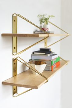 soudasouda:  Strut Shelving System by Souda Strut is a wall-mounted shelving system that consists of metal brackets and hard-wood shelves. Inspired by bridge construction and early aircraft carriers, the design is architectural, whimsical, and quite strong! The brackets are available in white, black, light blue, green, red, copper and brass (shown). The shelving is available in natural maple (shown), black, or white finishes. Follow Souda on Tumblr here