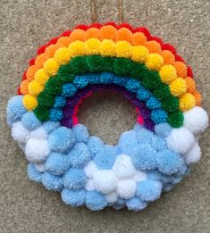 Rainbow and cloud pom pom wreath. With a total of 196 pom poms, this wreath has been lovingly made with all the colours of the rainbow. Perfect addition to a nursery or to brighten any room in the house! Approx in diameter with a jute yarn hanging loop. Pom Pom Rug, Pom Pom Wreath, Diy Wreath, Pom Poms, Wreath Crafts, Tulle Poms, Tulle Tutu, Cute Crafts, Yarn Crafts