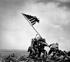 Iwo Jima flag raising during WWII. 3 of the 6 who raised the flag while being fired upon- Strank, Block, and Sousley- would die shortly after the photo was taken.