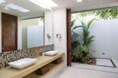 El baño principal de la casa se abre generosamente hacia un jardín a través de puertas correderas tejidas en madera mataba. Por otra parte, la iluminación natural está puntualizada por medio de una ranura en el techo que filtra la luz al interior.