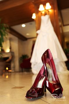 Brightly coloured shoes in front of the hanging wedding dress - want this picture