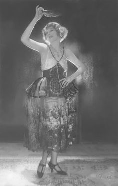 c.1921 Baron de Meyer ,Ina Claire   Actress Ina Claire, standing with left hand on hip, holding a fan overhead, and wearing her costume from the play 'The Gold Diggers,' a dark net, bouffant dress from Bendel.