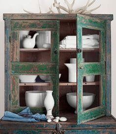 Distressed wood can work wonders in a shabby-chic home. Fill it with white porcelain for a unified feel. Love that cupboard...