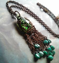 "A whimsical marriage of an antique emerald green chandelier crystal adorned in brass filigree and accented with fringe of turquoise nuggets.The pendant is 3 plus inches including the fringe.20"" chain that is adjustable down to choker length."