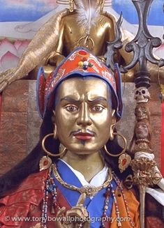 Padmasambhava/Guru Rimpoche who brought Buddhism to Tibet. Detail of image created by Chintamani and others for a 10 day Buddhist Convention in the 1980s. Seen with his trident in front of other Buddha forms/rupas in the main shrine/meditation hall.
