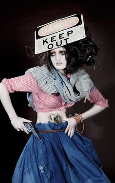 Barbed wire and a Danger sign here compliment the full recycled denim skirt by Gary Harvey