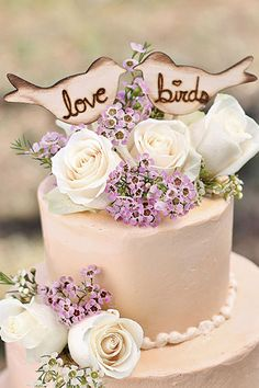 A love-bird cake topper adds a sweet touch to the wedding cake.Photo courtesy of Rustic Chic Weddings