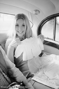 A pregnant Sharon Tate holding up a baby's jumper. This was taken three days before she was murdered, 1969.