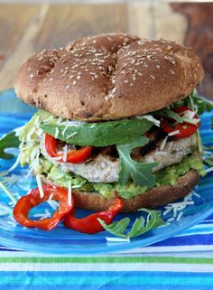 Mustard Turkey Burgers: 1 pound ground turkey  1 tablespoon Dijon mustard  1/4 cup minced red onion  1 teaspoon coarse salt  Extra-virgin olive oil, for drizzling  4 whole-wheat buns, grilled  1 avocado, sliced  4-5 Peppadew peppers, sliced  1 cup baby arugula  1/4 cup grated Parmesan