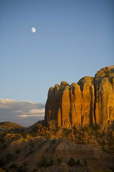 Moon seen during the day over sandstone cliffs in Abiquiu, New Mexico; photo by Ralph Lee Hopkins